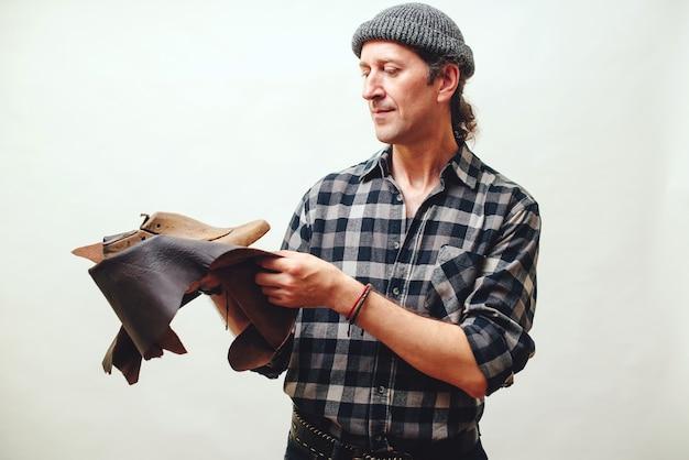 Handwerker, der neuen schuh in seiner werkstatt modelliert. small business-konzept. handgemachte lederschuhe. schuster, der satz werkzeuge und leder hält