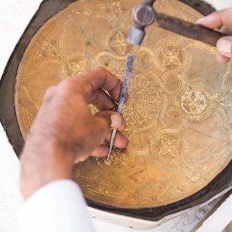 Handwerker-gravurmuster auf dem tablett. meister zentralasiens. manuelle kupferprägung