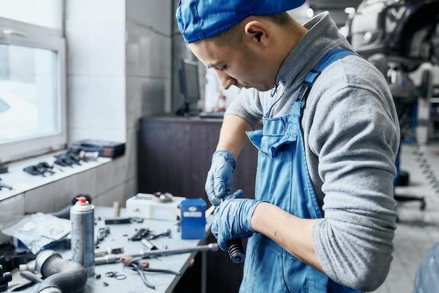 Handwerker im autoservice, der mit kleinen details auf dem tisch arbeitet