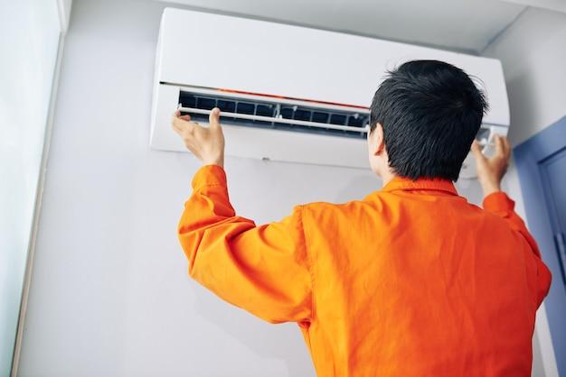 Handwerker in orangefarbener uniform, der die klimaanlage in der wohnung des kunden installiert oder überprüft
