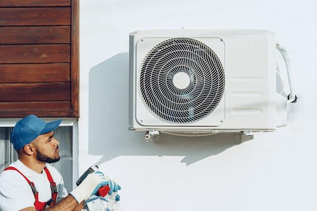 Handwerker in uniform, der die außeneinheit der klimaanlage installiert