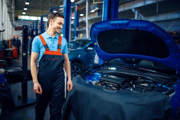 Handwerker in uniform steht am fahrzeug mit geöffneter motorhaube, autotankstelle. überprüfung und inspektion von kraftfahrzeugen, professionelle diagnose und reparatur
