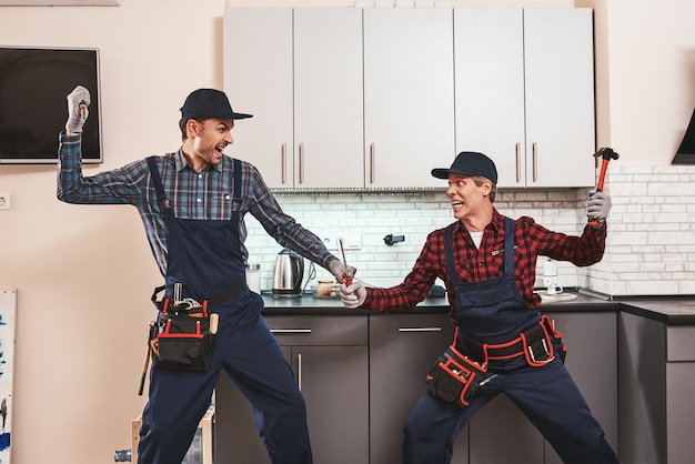 Handwerker männer kämpfen lustiges foto von zwei mechanikern, die mit schraubenziehern kämpfen screwdriver