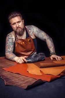 Handwerker mit bart und tätowierungen überall in seinem arbeitsbereich