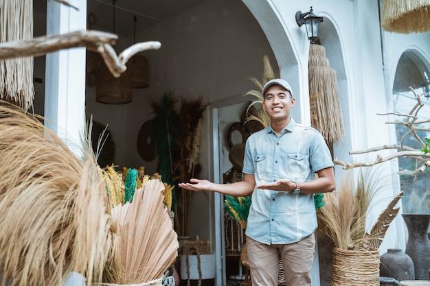 Handwerker mit einer handbewegung präsentiert etwas vor einem handwerksladen