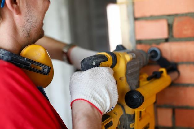 Handwerker mit elektrischer maschine, der schutzhandschuhe trägt