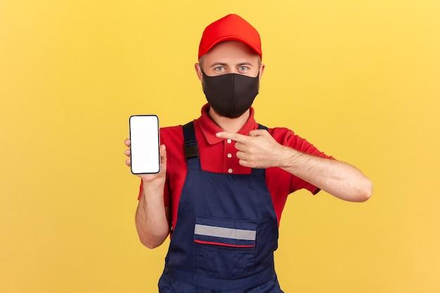 Handwerker mit schutzmaske im gesicht, der mit dem finger auf das smartphone mit leerem display zeigt