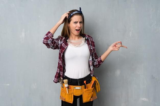 Handwerker oder elektriker frau überrascht und finger auf die seite zeigen