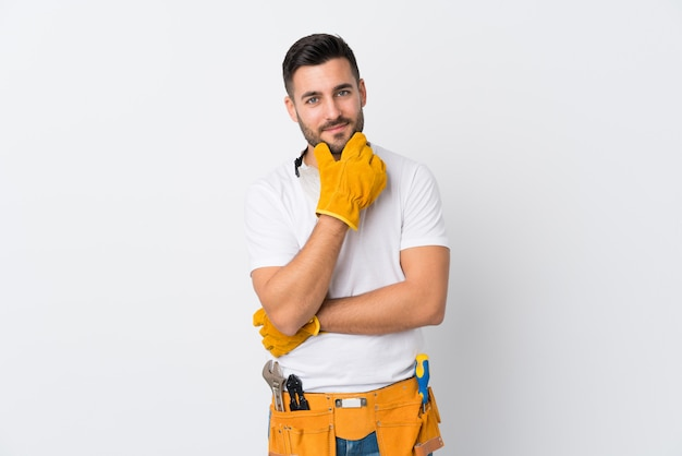 Handwerker oder elektriker über isolierte weiße wand, die eine idee denkt