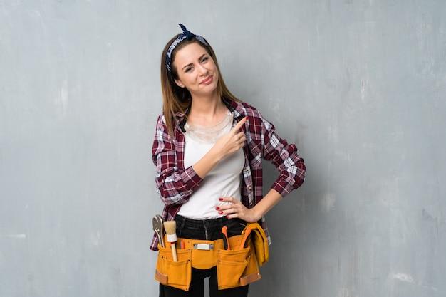 Handwerker- oder elektrikerfrau, die auf die seite zeigt, um ein produkt zu präsentieren