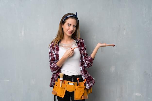 Handwerker- oder elektrikerfrau, die copyspace auf der palme eingebildet hält, um eine anzeige einzufügen