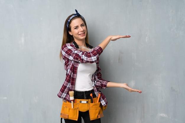 Handwerker- oder elektrikerfrau, die copyspace hält, um eine anzeige einzufügen