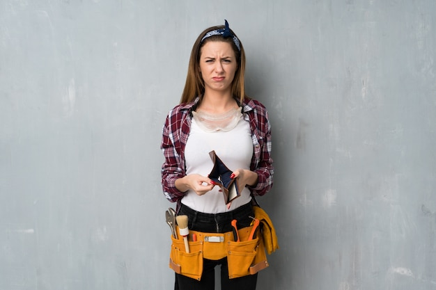 Handwerker oder elektrikerfrau, die eine geldbörse hält