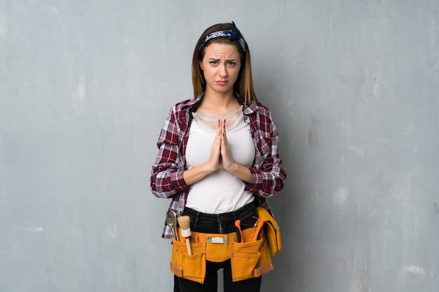 Handwerker- oder elektrikerfrau hält palme zusammen. person bittet um etwas