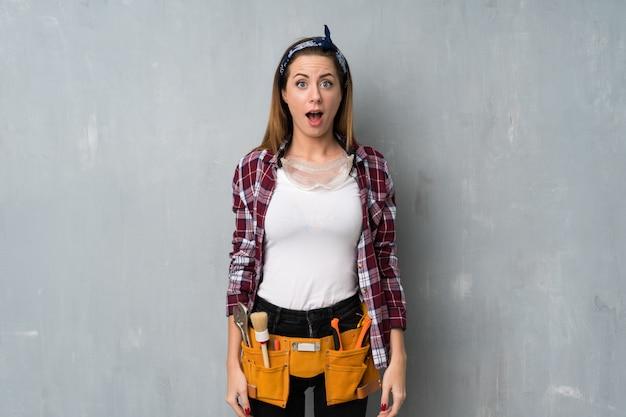 Handwerker oder elektrikerfrau mit überraschungsgesichtsausdruck