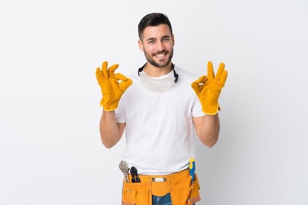 Handwerker oder elektrikermann über der lokalisierten weißen wand, die ein okayzeichen mit den fingern zeigt