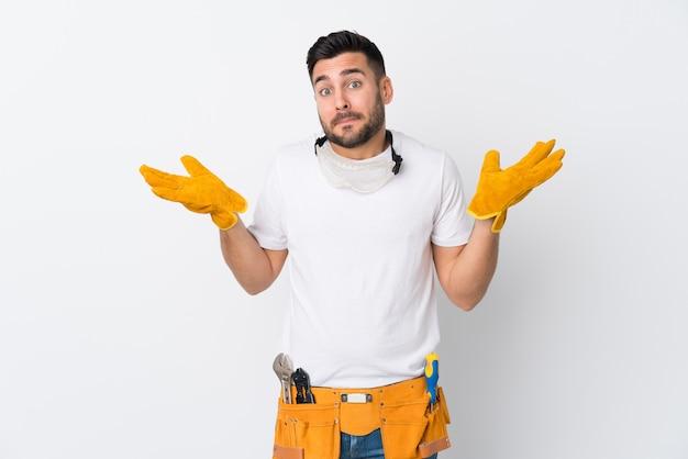 Handwerker oder elektrikermann über der lokalisierten weißen wand, die zweifel mit hat, verwirren gesichtsausdruck