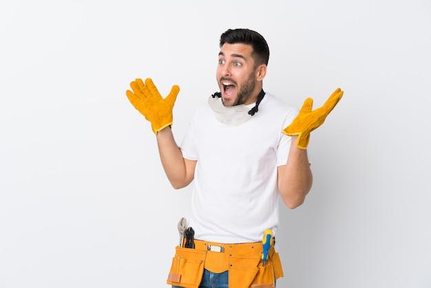 Handwerker oder elektrikermann über lokalisierter weißer wand mit überraschungsgesichtsausdruck