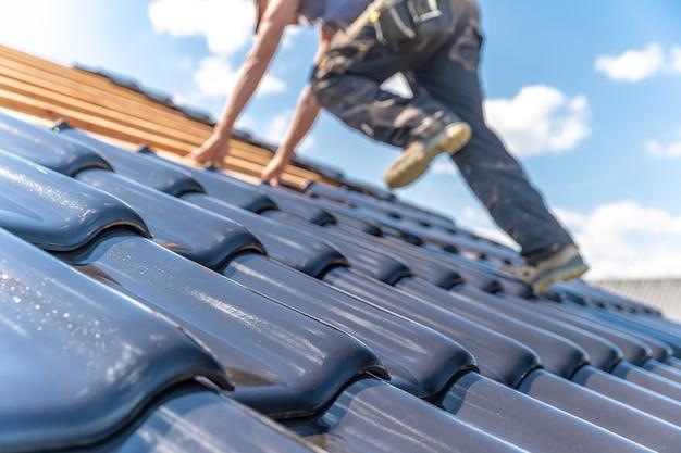 Handwerker schätzen eine gebrannte keramikfliese auf dem dach
