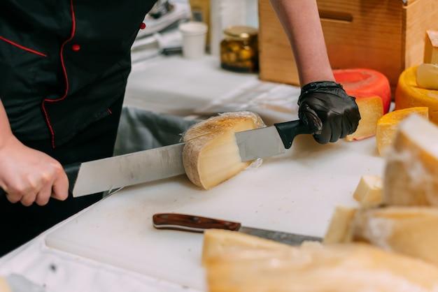 Handwerker schneidet handgemachten käse in einem geschäft.