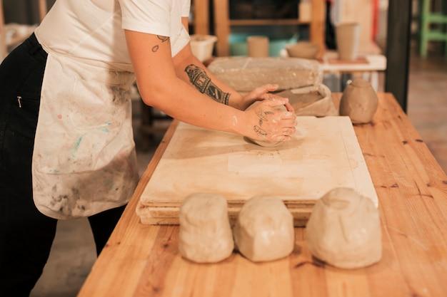 Handwerkerin, die den lehm auf hölzernem brett über der tabelle knetet
