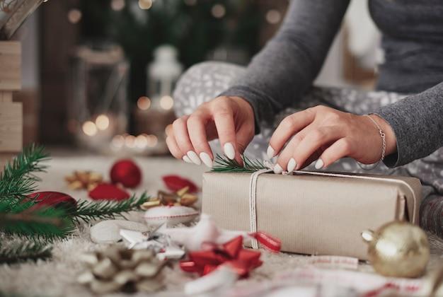 Handwerkerin, die ein verpacktes geschenk verziert