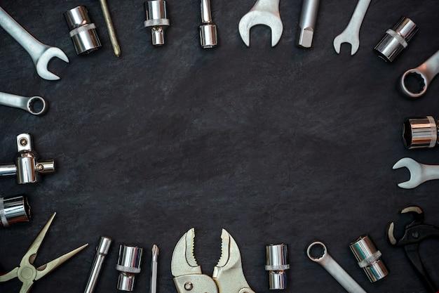 Handwerkerwerkzeug auf schwarzem zementhintergrund. exemplar. konzept der wartung wie bisher wiederverwendet werden.