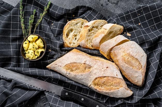Handwerkliche baguettes und scheibe mit butter schneiden. draufsicht