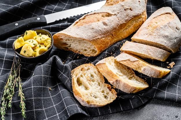 Handwerkliche baguettes und scheibe mit butter schneiden. schwarzer hintergrund. draufsicht