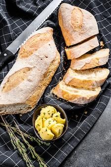Handwerkliche baguettes und scheibe mit butter schneiden