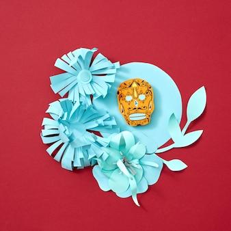 Handwerkliche papierblumen und -blätter verzieren den blauen rahmen mit calaveras attribut des mexikanischen feiertags von calaca auf einem roten hintergrund mit platz für text. kreative halloween-postkarte. flach liegen