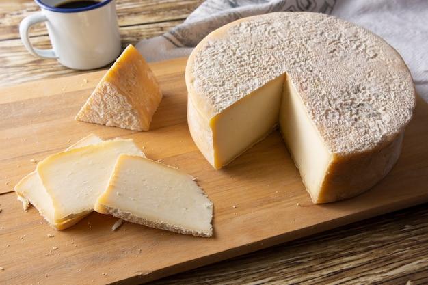 Handwerklicher canastra-käse von minas gerais, brasilien mit kaffeetasse über holztisch
