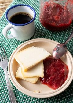 Handwerklicher canastra-käse von minas gerais, brasilien mit kaffeetasse und erdbeergelee über grünem und weißem gewebe auf einem holztisch