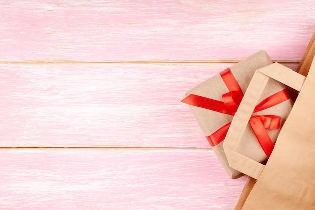 Handwerks-papiertüte und geschenkbox mit rotem band-bogen und herzen auf rosa hintergrund