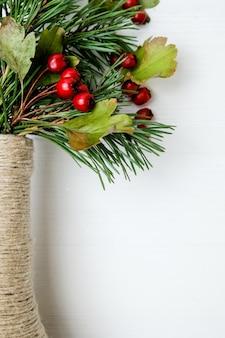 Handwerksflasche gebunden mit schnur mit weihnachtsbaumasten und weißdorn