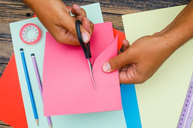 Handwerkskonzept mit werkzeugen auf hölzernem hintergrund flach legen. mann schneidet herz aus papier.