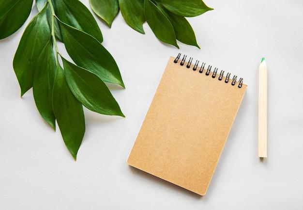 Handwerksnotizbuch und grüne blätter