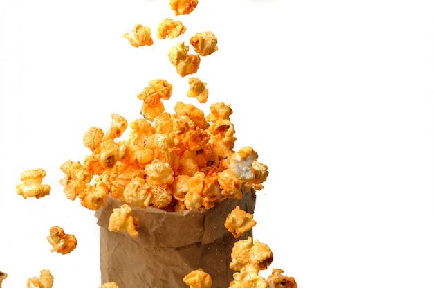 Handwerkspapiertüte des köstlichen popcorns auf weiß
