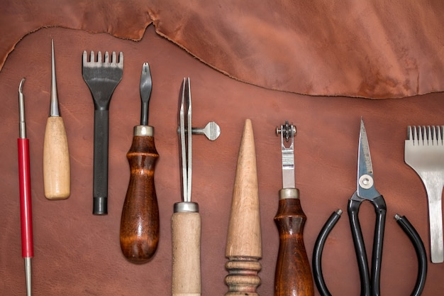 Handwerkszeug und braune lederstücke. layout über die herstellung von lederwaren. von oben betrachten