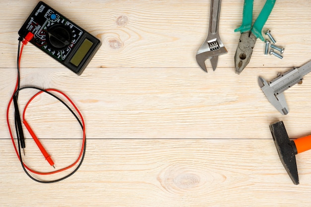 Handwerkzeuge und multimeter auf holzbrettern