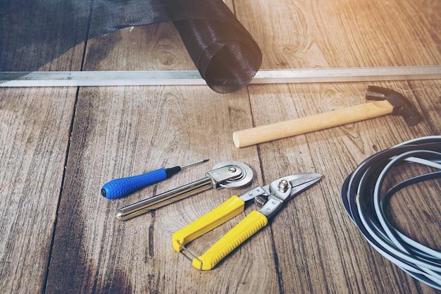 Handwerkzeugset und beschädigter moskitodrahtschirm, der repariert werden muss