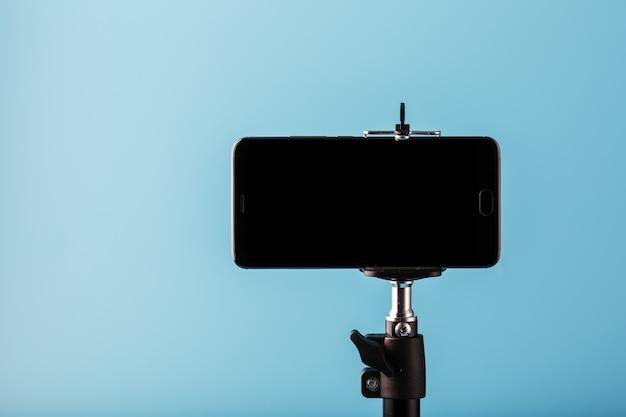 Handy auf einem stativ mit einer klaren schwarzen anzeige für bild und text, blauer isolierter hintergrund.