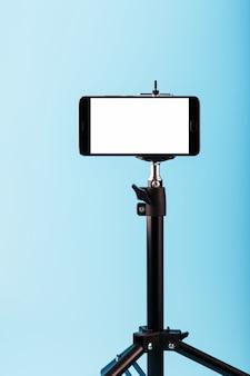 Handy auf einem stativ mit einer klaren weißen anzeige für bild und text, blauer isolierter hintergrund.