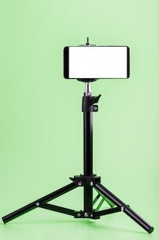 Handy auf einem stativ mit einer klaren weißen anzeige für bilder und text, grüner isolierter hintergrund.
