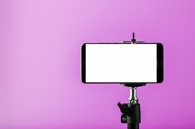 Handy auf einem stativ mit einer klaren weißen anzeige für bilder und text, rosa isolierter hintergrund.