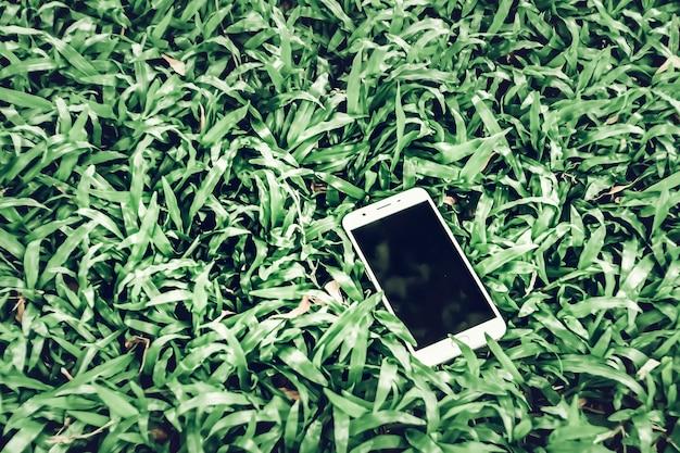 Handy auf grünem gras. arbeiten im freien überall lifestyle. machen sie das leben einfacher mit dem hintergrund der technologiekonzeptidee. mock-up für gutschein-qr-code auf dem smartphone