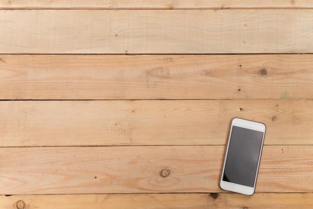Handy auf plankenholztisch des brauns, kopienraum, draufsichwinkel, für darstellungsprodukt