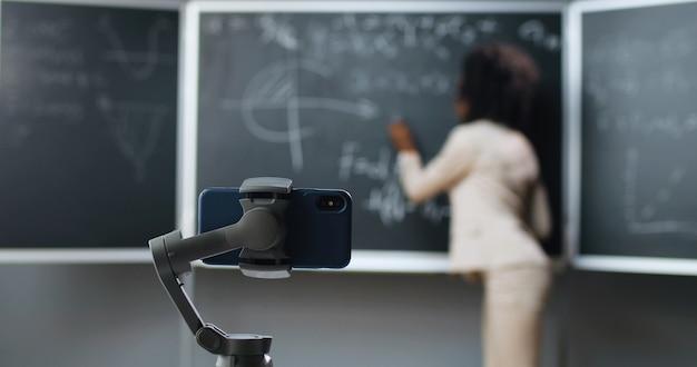 Handy-aufzeichnung online-video-lektion in der schule. lockdown isoliert studieren. afroamerikanische lehrerin, die mathematik- oder physikformeln im unterricht an der tafel erklärt. pandemie bildung.