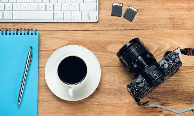 Handy, computertastatur, stift und notizblock für notizen, kaffeetasse, flash-laufwerke und kamera auf einem holztisch. gegenstände des fotografen am arbeitsplatz.
