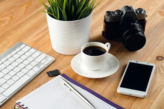Handy, computertastatur, stift und notizblock für notizen, kaffeetasse, flash-laufwerke und kamera auf holztisch.